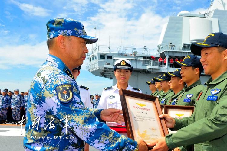 海军副司令丁毅中将为取得航母资质认证的舰载机飞行员颁发证书。